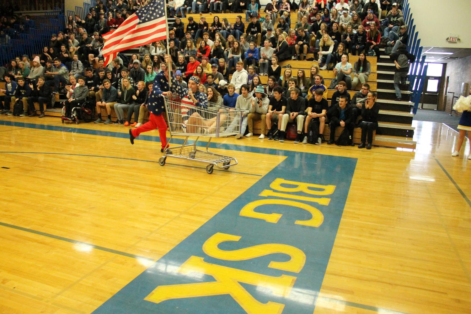 Student body presidents enter using a shopping cart with a United States Flag  and dressed in all American Flag outfits.