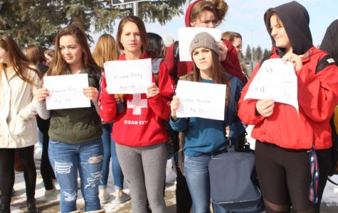 Five students hold paper signs reading