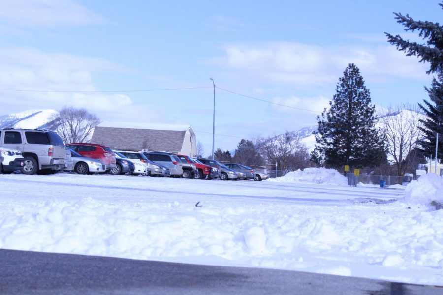 parking lot with snow and parked cars