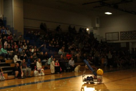 Big Sky's Robotic's team shoots shirts with one of their robots during the assembly.