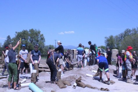 Group of students putting sand into bags.