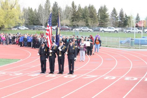 uniformed men and women carry a flag on a red track.