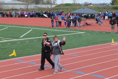A young woman waves while walking on a track with an officer escorting her.