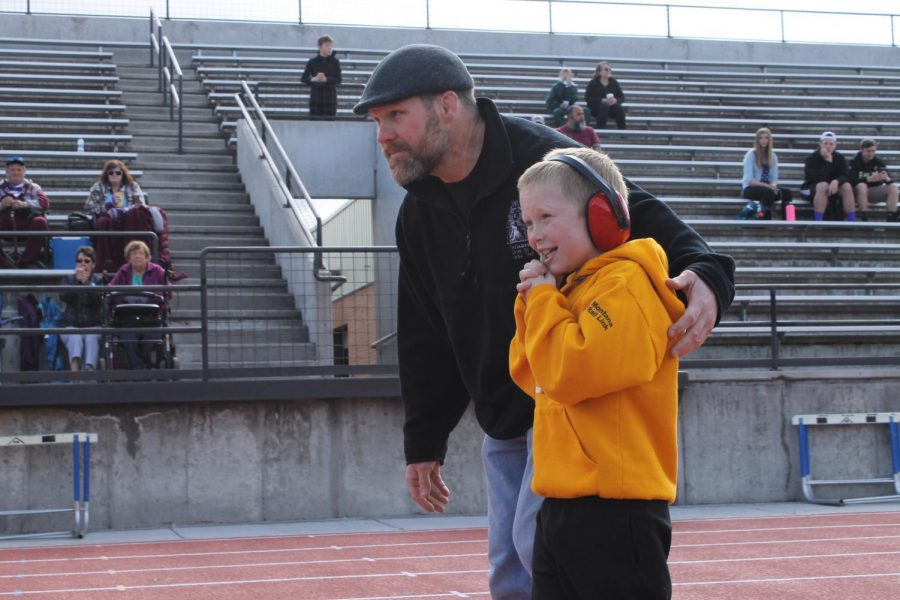 A young child in a yellow jacket smiles while a man encouragingly hugs him.