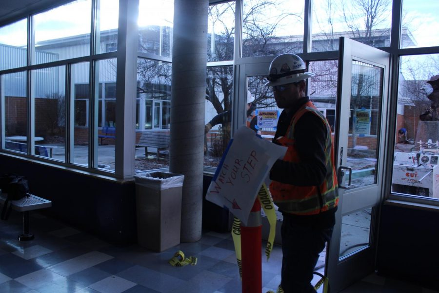 worker in a hat and orange vest inside the school