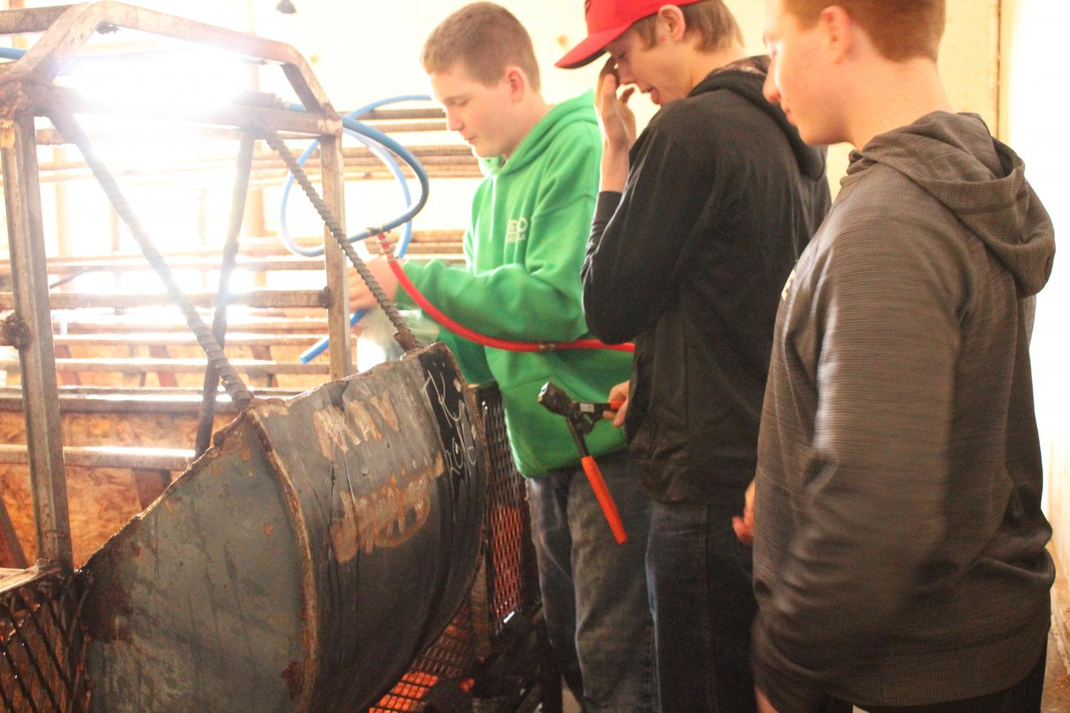 Freshmen Ryan Shields, Blake Weingart, and Hunter Hayden fix hoses for the pigs' water feeder in AG class.