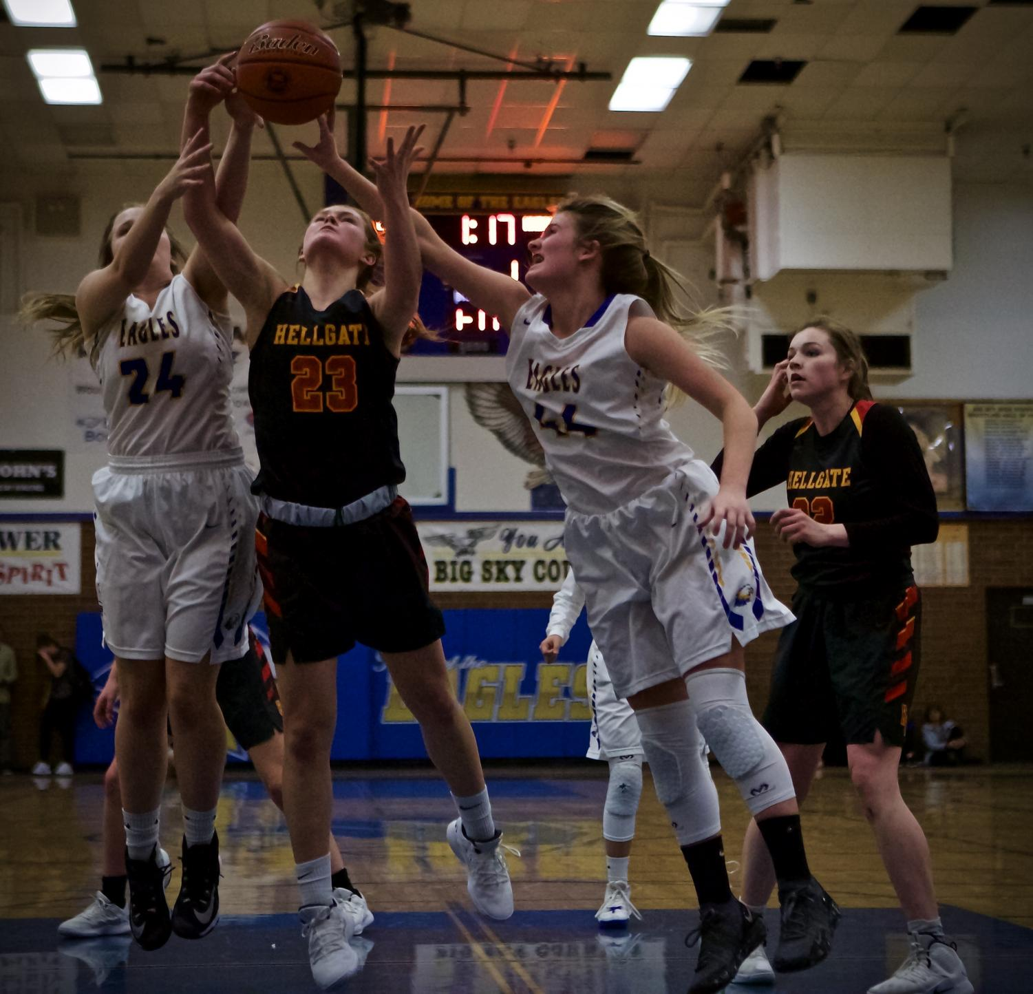 Senior Reagan Shoupe and Freshman Avari Batt attempt to block a Hellgate shooter at a home game where the Eagles fell 33-55.