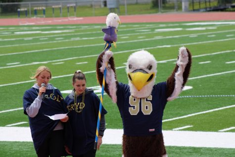 School president candidates campaign next to Eddy the Eagle.
