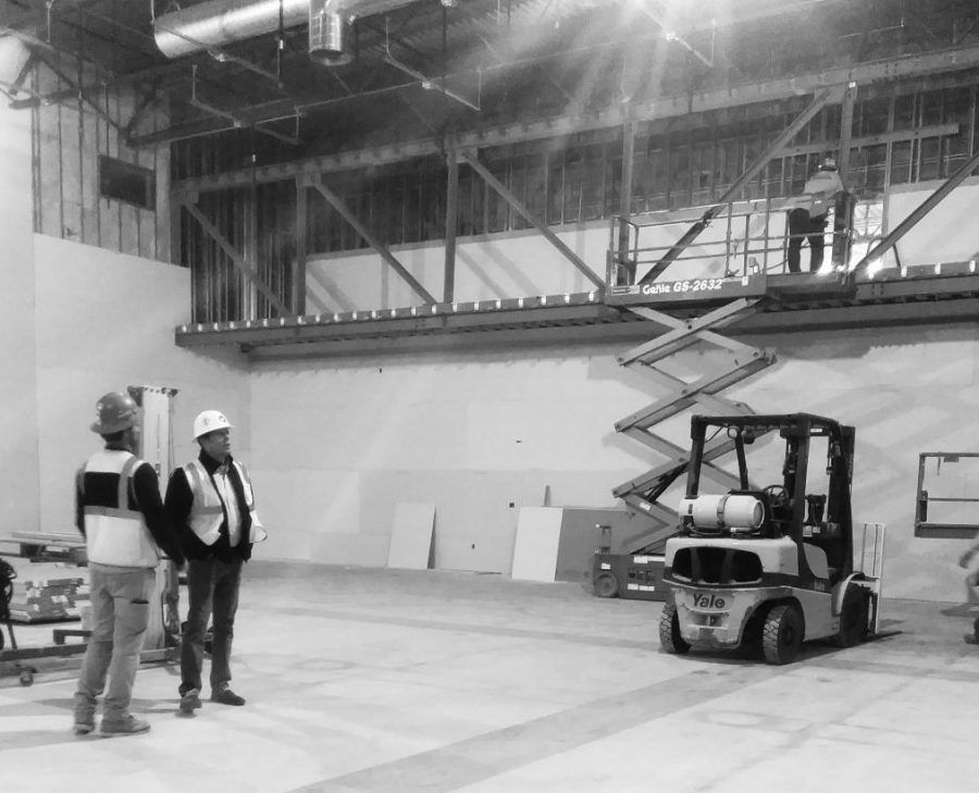 Construction+workers+examine+the+framing+for+the+new+and+improved+light+booth+in+the+auditorium.++