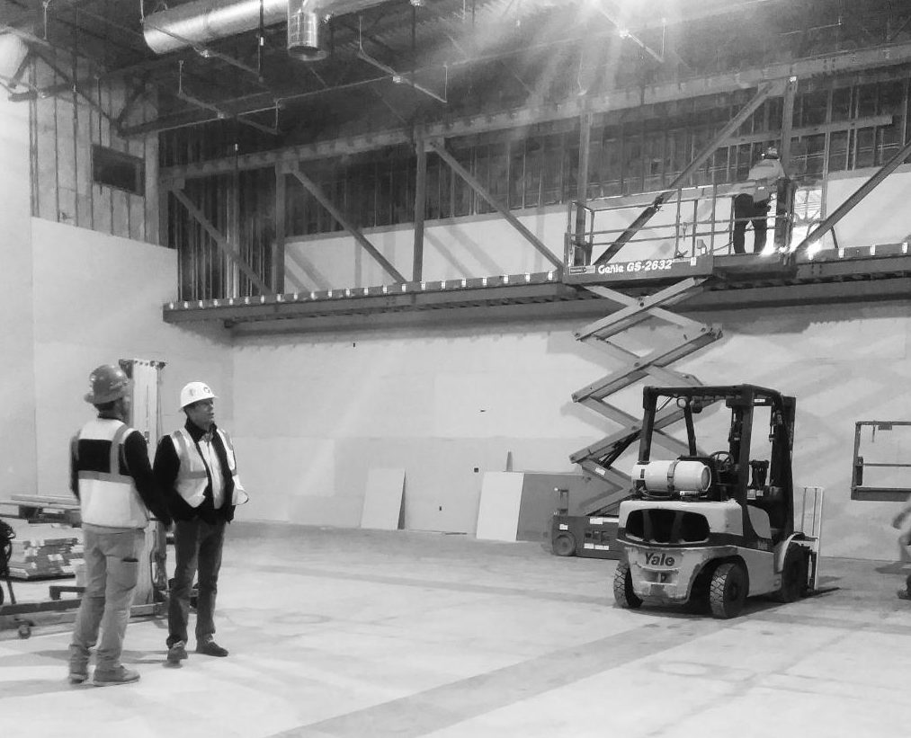 Construction workers examine the framing for the new and improved light booth in the auditorium.