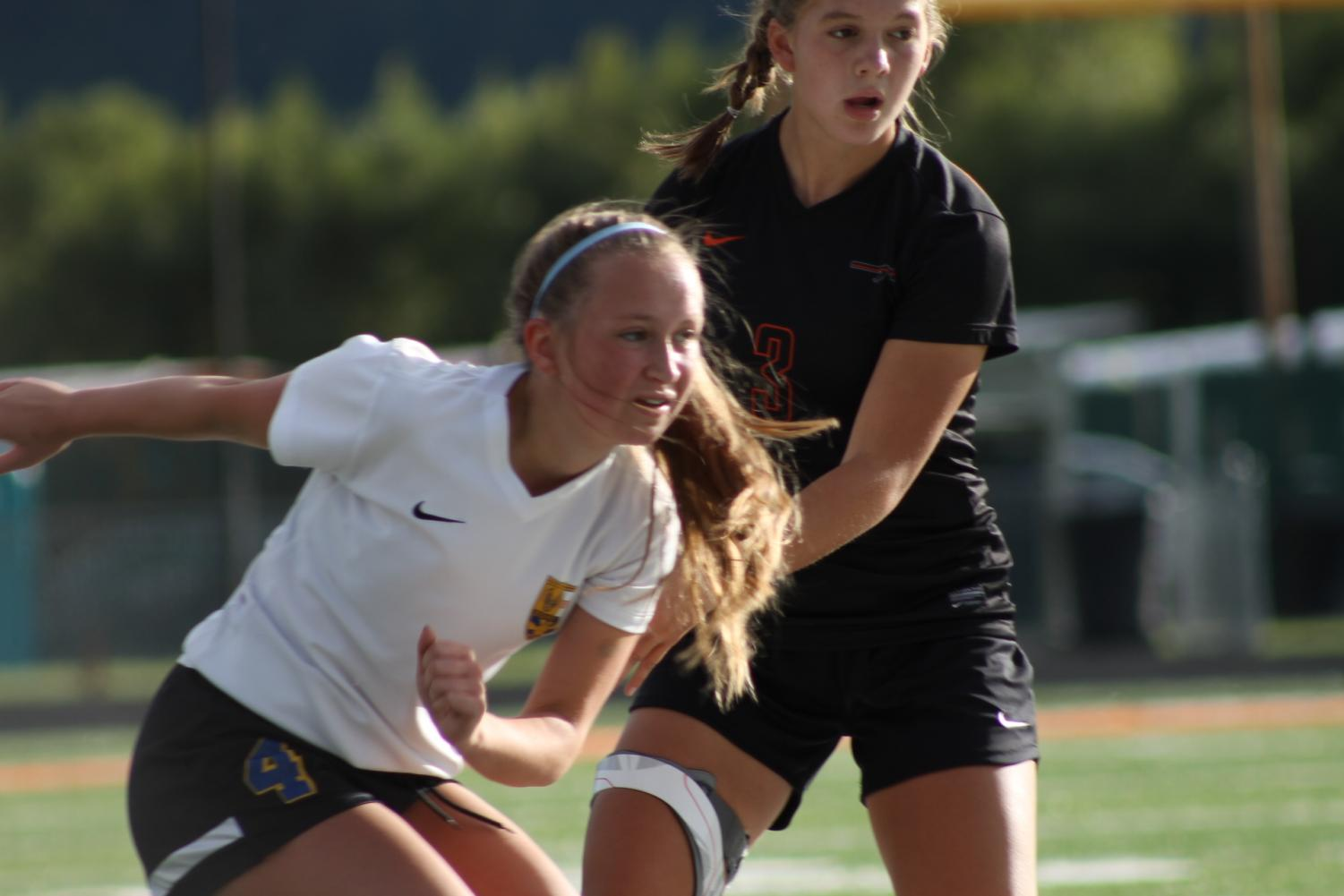 Annie Migliaccio races to the ball while a defender hovers behind her.