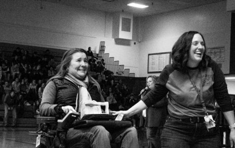 Two woman smiling in an auditorium