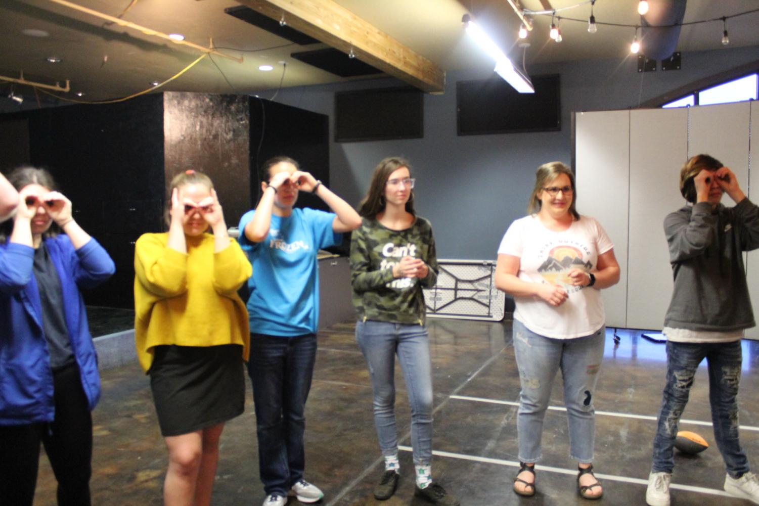 students standing in a rowmaking goggles with their hands