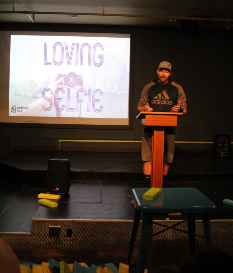 A man at a podium in front of a presentation reading love your selfie