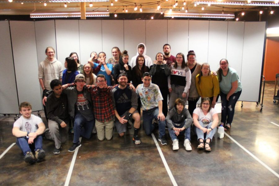 around 25 teens and adults pose in a group